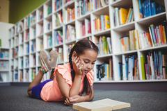 Girl lying and reading a book - stock photo