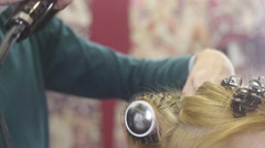 Barber raise roots of hair to blonde girl by comb and hairdryer in beauty saloon - stock footage