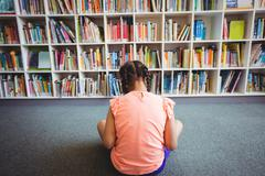 Rear view of girl reading a book - stock photo