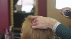 Professional barber comb top of hair to blonde girl in beauty saloon. Making - stock footage