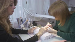 Manicurist polish surface nails to attractive woman by nail apparatus in saloon - stock footage