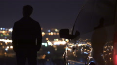 The man stand near the car on the background of blur light. Real time capture Stock Footage
