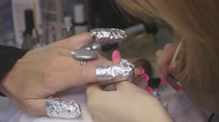 Professional manicurist put white lacquer on designed nails by brush in beauty Stock Footage