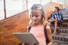 Cute little schoolgirl looking at her digital tablet - stock photo