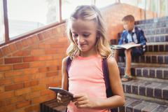 Cute little schoolgirl looking at her smartphone - stock photo