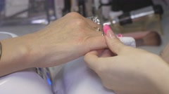Professional manicurist put off shellac cover from nails of woman in beauty Stock Footage