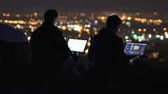 The men work at the laptop on the background of blur light. Real time capture Stock Footage