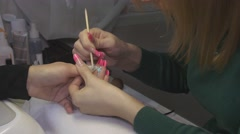 Manicurist put off cover from surface of nails in beauty saloon by orange stick Stock Footage