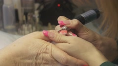 Manicurist remove lacquer from nail surface in beauty saloon by apparatus Stock Footage