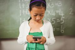 Schoolgirl using her smartphone - stock photo