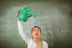 Schoolgirl using a watering can - stock photo