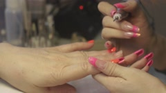 Master purge off cover from nail surface to client in beauty saloon by apparatus - stock footage