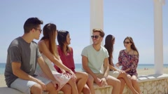 Young friends sitting on stone wall near beach Stock Footage