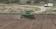 Agriculture farm tractor planting seed in field away DCI 4K Stock Footage