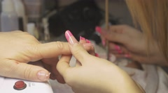 Manicurist put gel on nail of client in beauty saloon by brush. Nail extension Stock Footage
