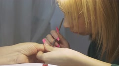 Manicurist put lacquer on nail of woman in beauty saloon by brush. Nail - stock footage