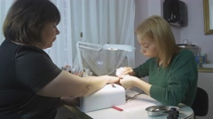 Professional manicurist treat nails of adult woman by napkin in beauty saloon Stock Footage