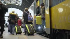Many passengers with suitcases leaving train and walking on railway platform Stock Footage