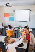 Teacher giving lesson to her students - stock photo