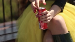 The girl in the yellow dress , leather jacket, drinking soda from a can Stock Footage
