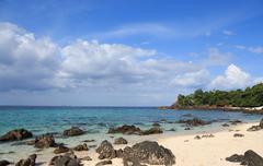 rough rock stone coastal in white bay beach island, blue sea sky - stock photo