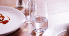 4K Water poured into drinking glass beside delicious plated meal in restaurant Stock Footage