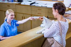 A woman vet giving a paper to her customer - stock photo