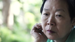 video of Asian senior woman with hand on face thinking, worry and sad - stock footage