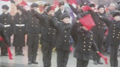 Many teens stay n in military uniform raise red flags in both hands. Audience Stock Footage