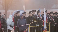 Many men in military uniform stay with people behind fence. Russian national Stock Footage
