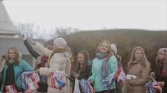 Many young girls wave blue pom pom, flags at road. Smile in camera. Event Stock Footage