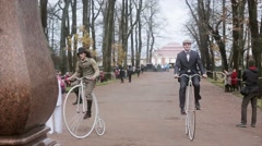 Two men ride on penny farthing bicycle in Peterhof State museum Reserve. Autumn Stock Footage