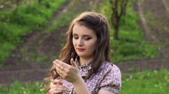 Young model with dandelion in hand looking on a camera. Slowly - stock footage