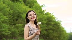 Smiling girl blowing dandelion, smiling and turning around on the nature. Slowly - stock footage