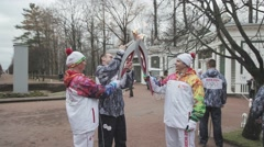 Relay race Olympic flame in Peterhof, Saint Petersburg. Torchbearer pass flame Stock Footage