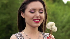 Brunette blowing dandelion and smiling on a camera. Slow motion Stock Footage