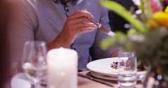4K Attractive mixed race man enjoying a delicious meal in restaurant & chatting  Stock Footage