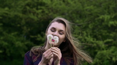 Happy girl blowing the bouquet dandelion in the garden. Slow motion - stock footage