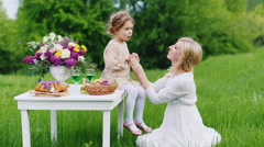 Mom plays with her daughter at a picnic. Girl sits on a white table with sweets - stock footage