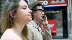 Man talking on cellphone and his girlfriend looking irritated, steadycam shot - stock footage