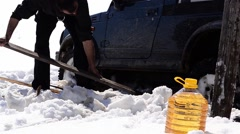 Worker removing snow with a plank from under a car stuck in drifts of snow Stock Footage
