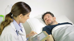 Man looking female doctor in hospital showing analysis on tablet medium shot - stock footage