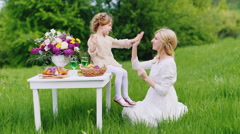 Mum with a daughter 4 years are pinned on a picnic. Girl sitting on the table Stock Footage
