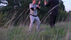The fighting of Wing Chun between masters through the grass in 4k Stock Footage