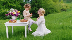 Girl 4 years old playing with his mother - feeds her a cupcake. She sits on the Stock Footage