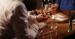 4K Happy attractive couple in a restaurant raise their wine glasses for a toast Stock Footage