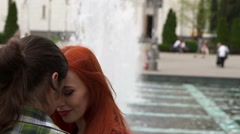 Couple sitting by the fountain near the church Stock Footage