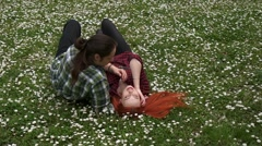 A couple in love lying in spring grass and flowers Stock Footage