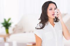 Composite image of asthmatic brunette using her inhaler - stock photo