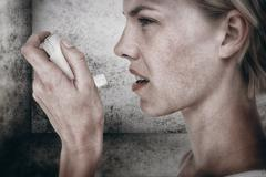 Composite image of asthmatic pretty blonde woman using inhaler - stock photo